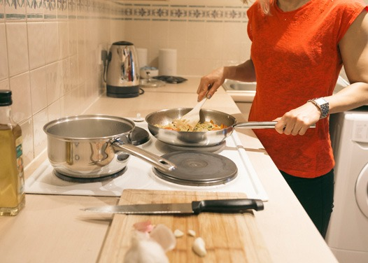 A woman cooking dinner while on a business trip